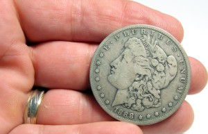Hand Holding Old Silver Dollar