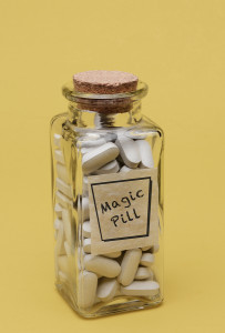 Closeup of an old fashioned pill bottle filled with Magic Pills.